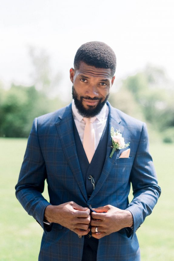 black groom with clean cut hair, full moustache and beard, wearing a plaid royal blue coat, plain blue waistcoat, pink necktie, white shirt and small pink floral boutonniere outside Crathorne Hall Wedding Venue
