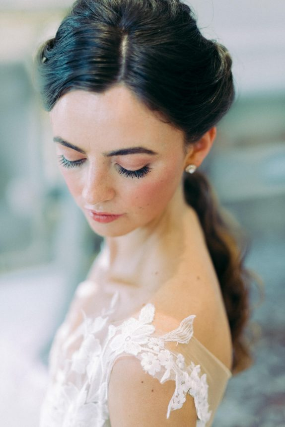 brunette bride with natural makeup and wearing a white lace sleeveless wedding dress while looking down