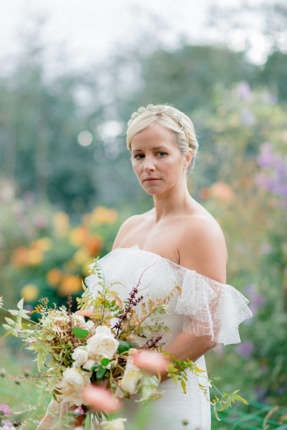half body photo of blonde bride with grey eyes wearing an agnes hart antique tiara crown, cherry williams london dress and a bouquet of spring flowers