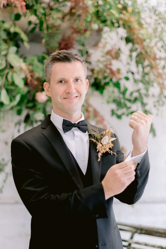 middle aged groom wearing a black formal coat with black waistcoat, white shirt and a black ribbon with dried flowers boutonniere