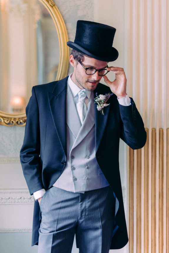 groom wearing a long black coat, grey waistcoat, white shirt with light blue necktie, black rimmed glasses and a black top hat at hedsor house near london