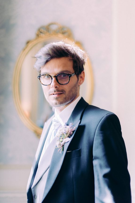 portrait of a groom wearing a black rimmed glasses long formal black coat with boutonniere