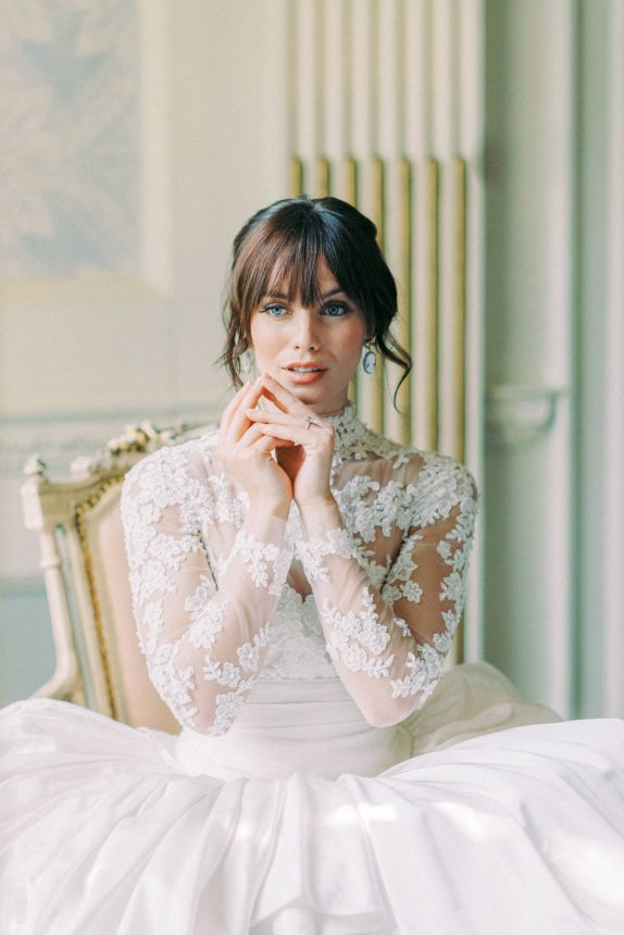 half body portrait of a brunette bride with full bangs and updo wearing lace marchesa wedding gown while sitting on an antique french chair at hedsor house