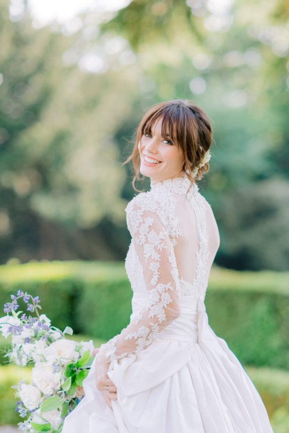 half body portrait of bride with bangs and loose updo smiling back and wearing a white traditional Marchesa wedding gown with spring bouquet of flowers