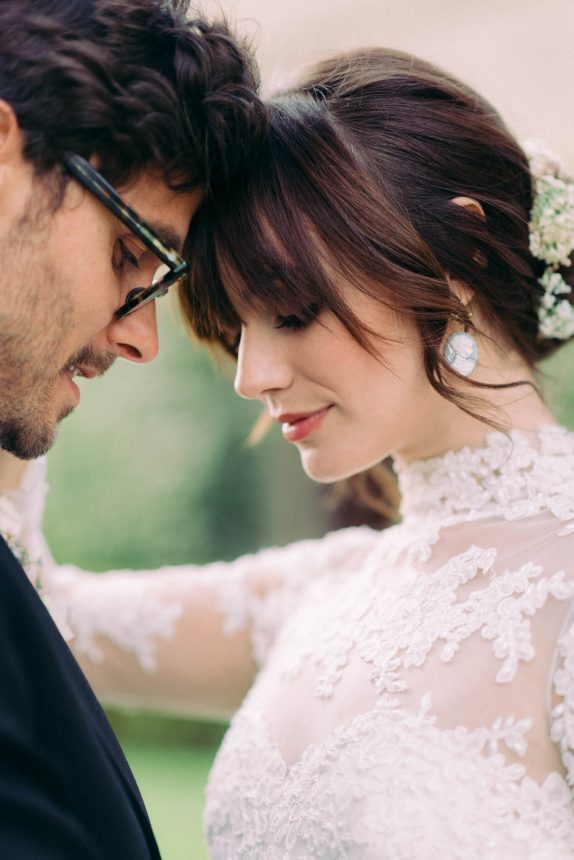 bride and groom portrait with foreheads touching each other and looking down. groom is wearing black rimmed glasses and bride is wearing a traditional marchesa lace wedding dress, flower bun, full bangs and cameo earrings