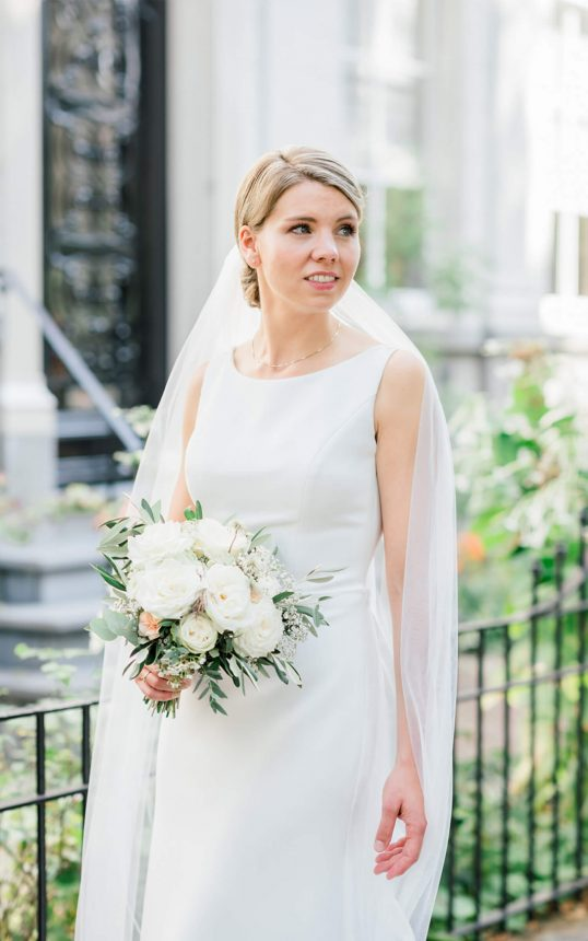 blonde bride looking and wearing a simple white wedding dress and white veil while holding a bridal bouquet of white roses in her right hand