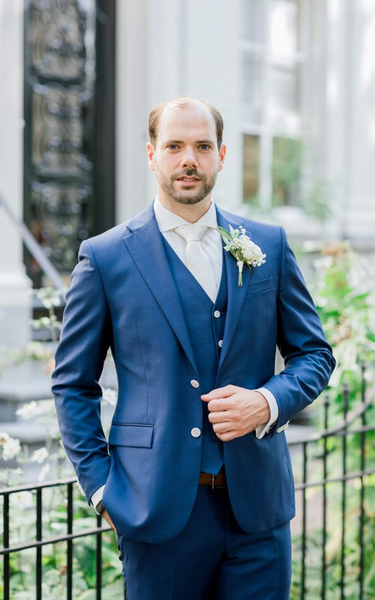 groom with dark brown hair with left hand holding his coat and wearing a blue suit with small boutonniere, white tie and shirt