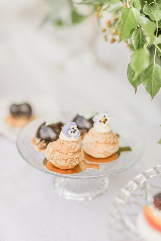 2019 Wedding Trend Luxury Patisserie Table: The Patisseria by MonAnnie Cakes and Alexandra Rose Weddings. A branding shoot at the Belmond Le Manoir Au Quat Saisons by Filipina fine art destination wedding photographer Cristina Ilao Photography | In Photo: Pineapple and caramel profiteroles, chocolate mouse domes, vintage glass cake serving dish