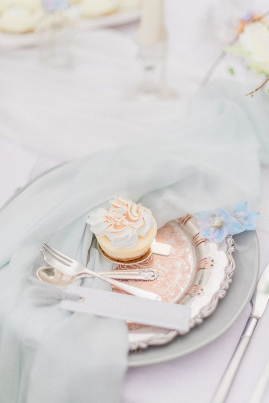 2019 Wedding Trend Luxury Patisserie Table: The Patisseria by MonAnnie Cakes and Alexandra Rose Weddings. A branding shoot at the Belmond Le Manoir Au Quat Saisons by Filipina fine art destination wedding photographer Cristina Ilao Photography | In Photo: Passion Fruit Meringue Cheesecake, pale blue silk table runner, vintage silver plate and pale grey ceramic plate, antique utensils, flat lay