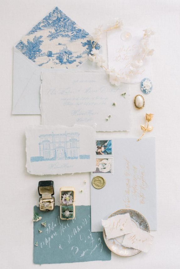 flatlay of a stationery suite by curved & co: handmade paper full wedding stationery suite and venue illustration of hedsor house, victor barbone antique jewellery on vintage victorian ring boxes, cameo and hair accessories