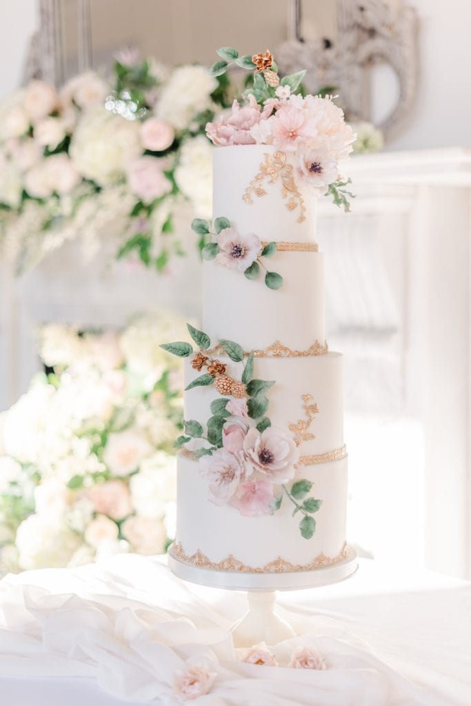 Elegant four tier fairytale wedding cake by Sadie May Cakes. With edible sugar flowers using a blush palette. Creative Team: Venue: Thicket Priory  Photography: Cristina Ilao Photography  Stationery: Katie Sue Design Co  Cake & desserts: Sadie May Cakes  Styling & floristry: Flori and Fern  Make-up: Amanda Bell  Hairstyling: Vicky Medhurst of Contemporary Yarm  Dress: Christian Alexander Bridal  Suit: Bakers Tailoring  Accessories: What Katy Did Next