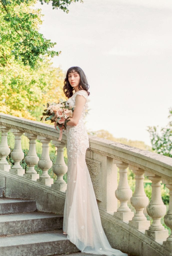 bride posing on top of the stairs and looking away from the camera. simple serpentine lace and tulle wedding gown by Duc Design. Photo by Cristina Ilao Fine Art Photography at the Hague