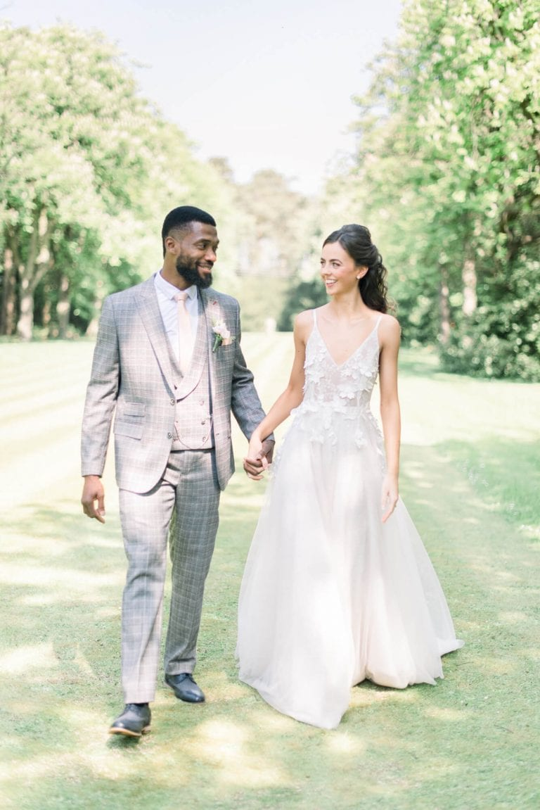 practical tips on how to choose your wedding photographer   In photo: bride and groom holding hands in English garden. bride wearing a simple A-line 3D floral applique wedding dress by Kate Fearnley and groom wearing a grey plain suit ensemble by Baker's Tailors. Captured by fine art destination wedding photographer Cristina Ilao
