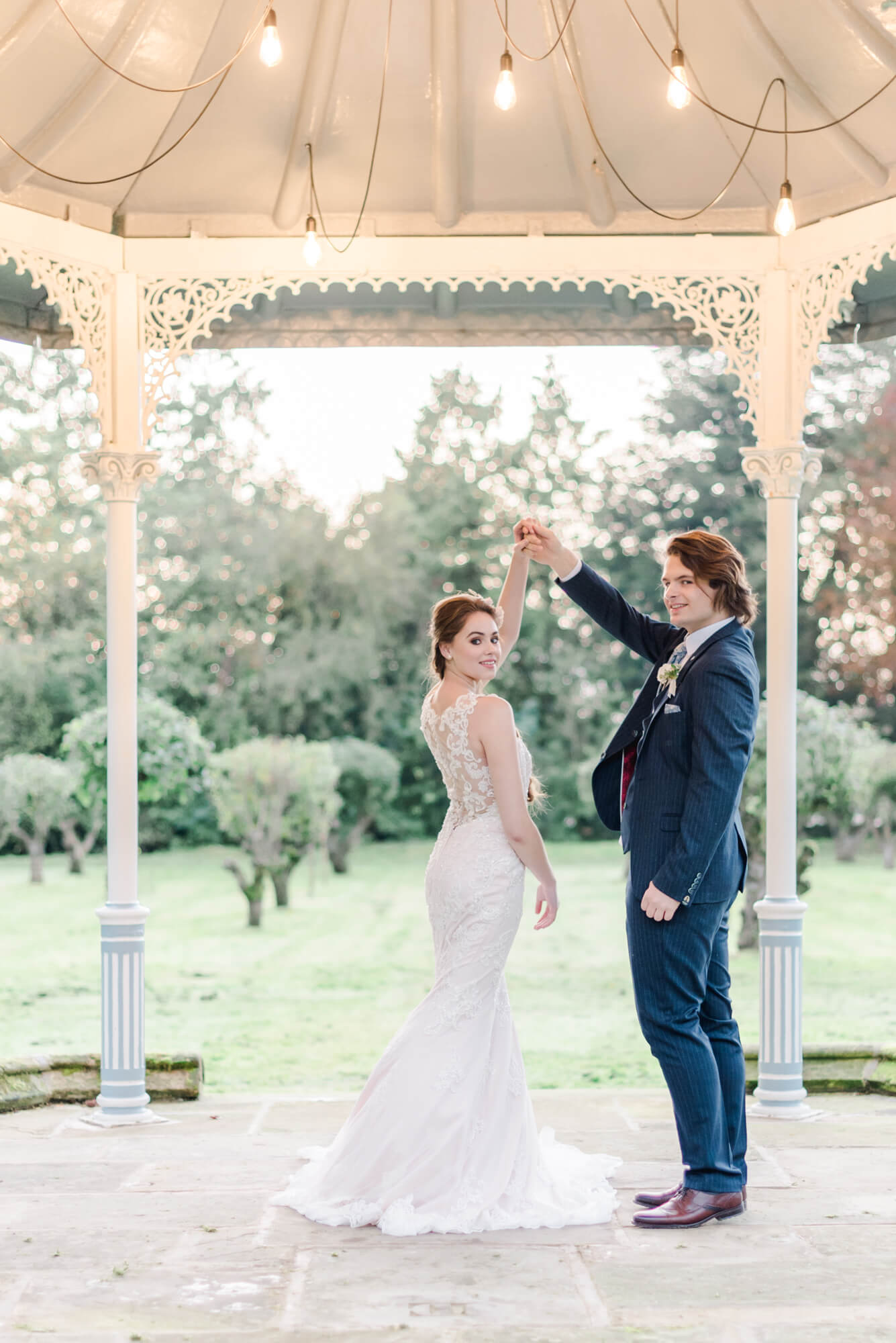 Practical tips on how to choose your wedding photographer. In Photo: bride and groom dancing under a gazebo at Thicket Priory Yorkshire. bride wearing an Ellis mermaid style wedding dress from Christian Alexander bridal boutique and grom wearing a dark blue suit ensemble from Baker's Tailoring. Shot at Thicket Priory by fine art destination wedding photographer Cristina Ilao | www.cristinailao.com