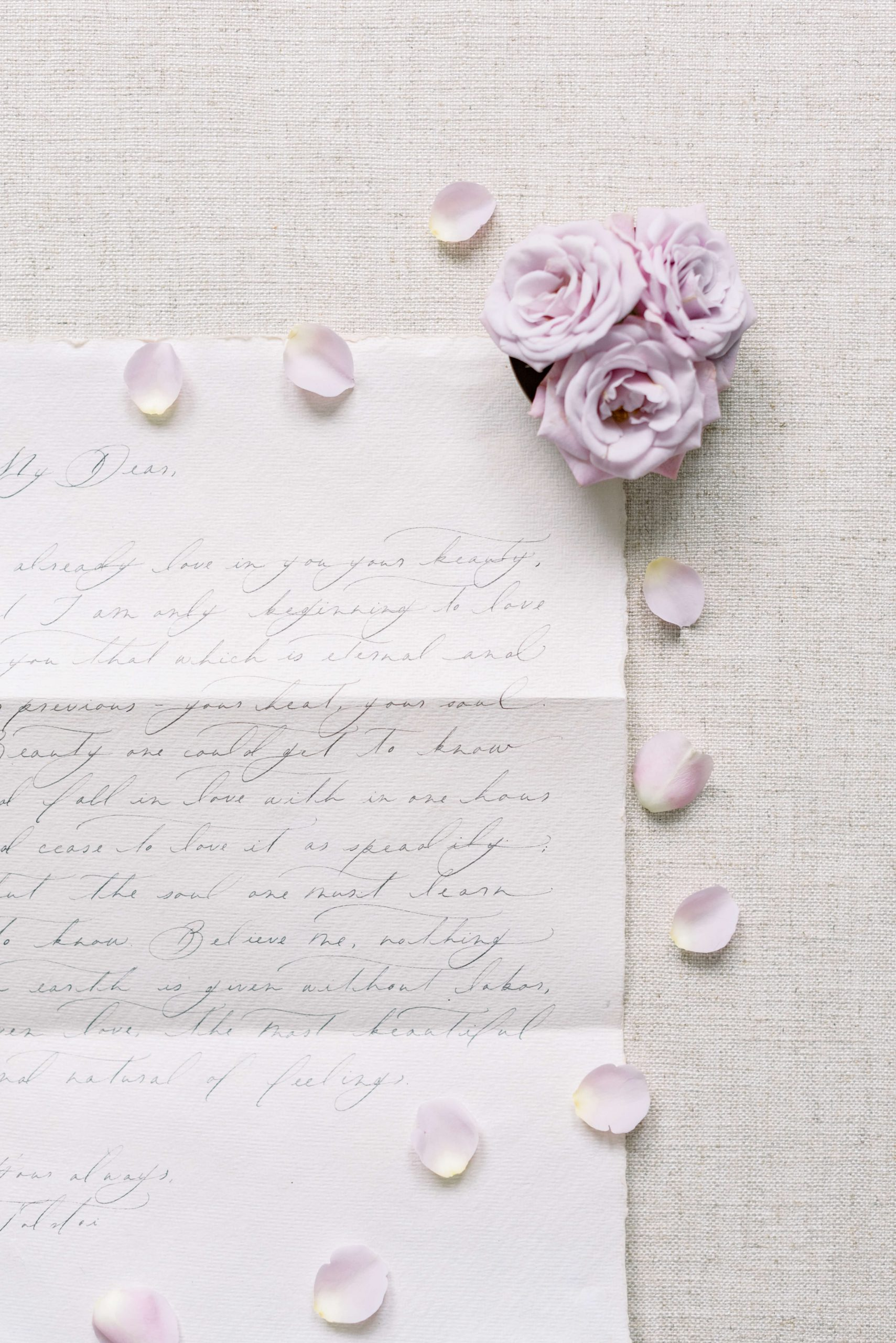 modern style calligraphy on handmade paper stationery by Vellume, three big mauve roses and scattered petals, linen flatlay styling board, Photo by Cristina Ilao www.cristinailao.com