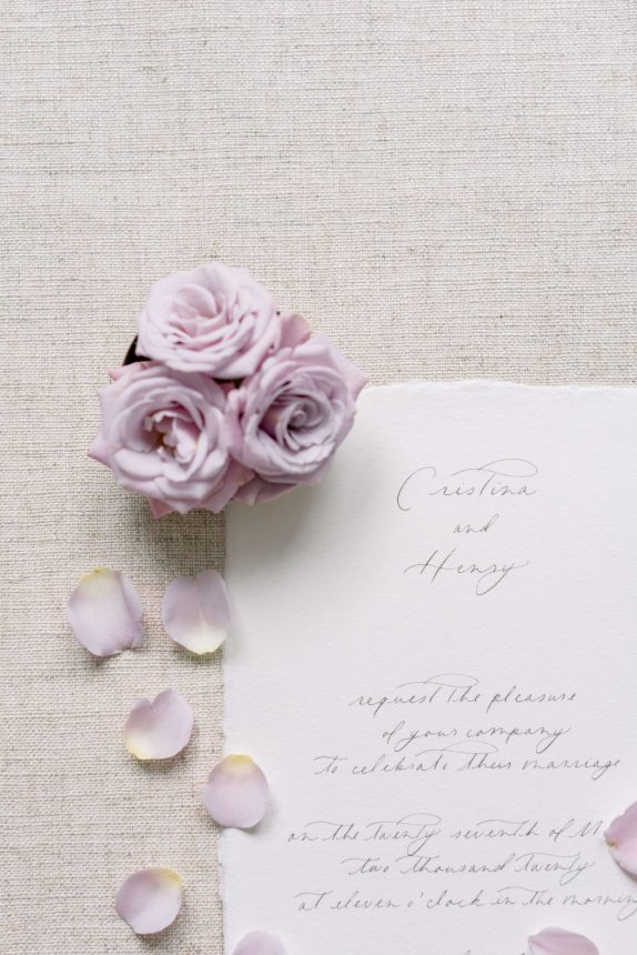 handmade paper wedding invitation flatlay with three mauve rosess and rose petals