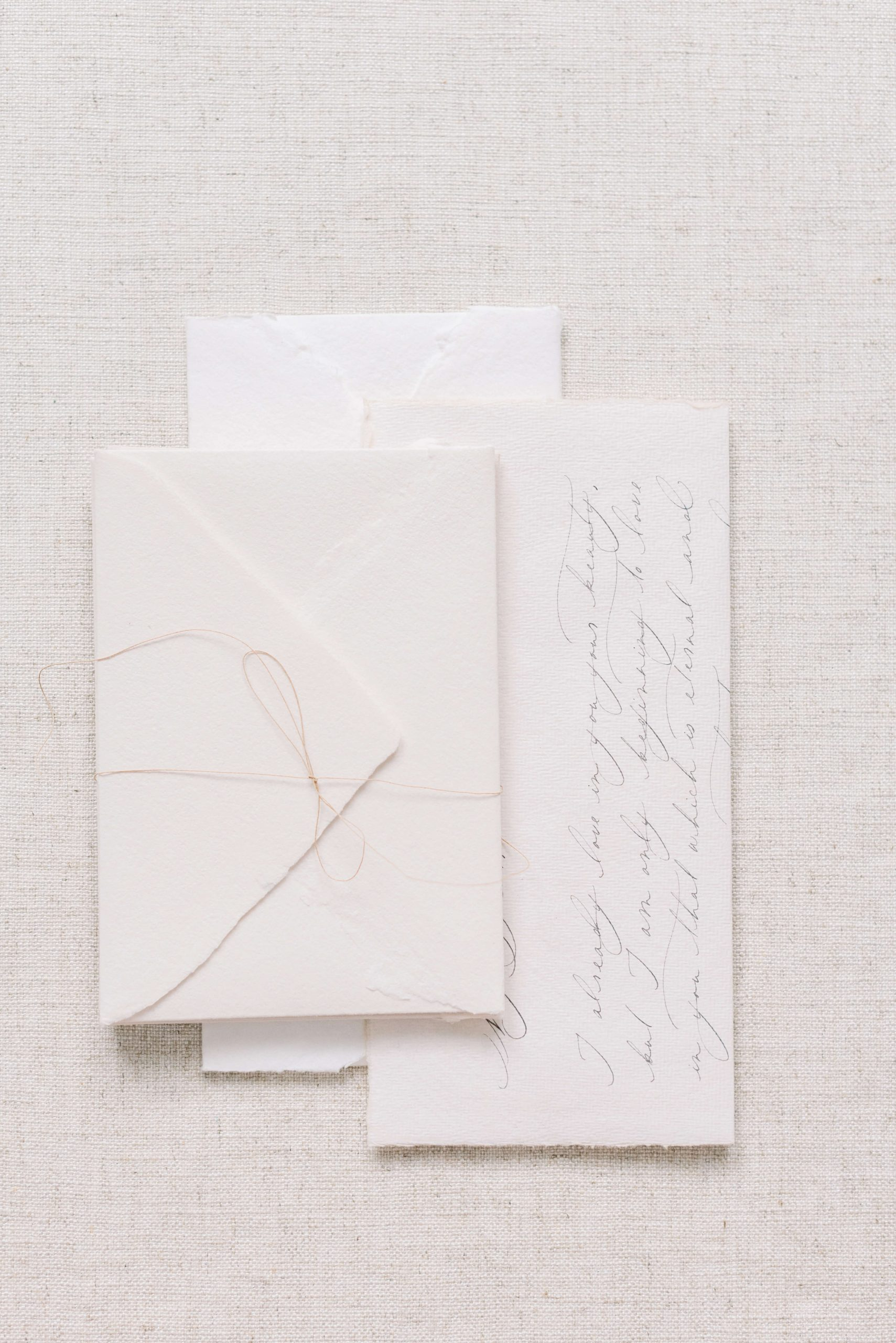 calligraphy on handmade paper with envelope tied with a string, linen styling board, Photo by Cristina Ilao www.cristinailao.com