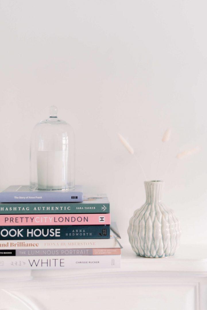 Pile of books including the story of Anne Frank (Anne Frank Museum), Hashtag Authentic (Sara Tasker), Pretty City London (Siobhan Ferguson), Brand Brilliance (Fiona Humberstone), The Luminous Portrait (Elizabeth Messina), For the Love of White (Chrissie Rucker), white candle covered by glass dome, Bloomingdale cracked glass teal vase with three pieces of bunny tails. Photo by Cristina Ilao Photography www.cristinailao.com