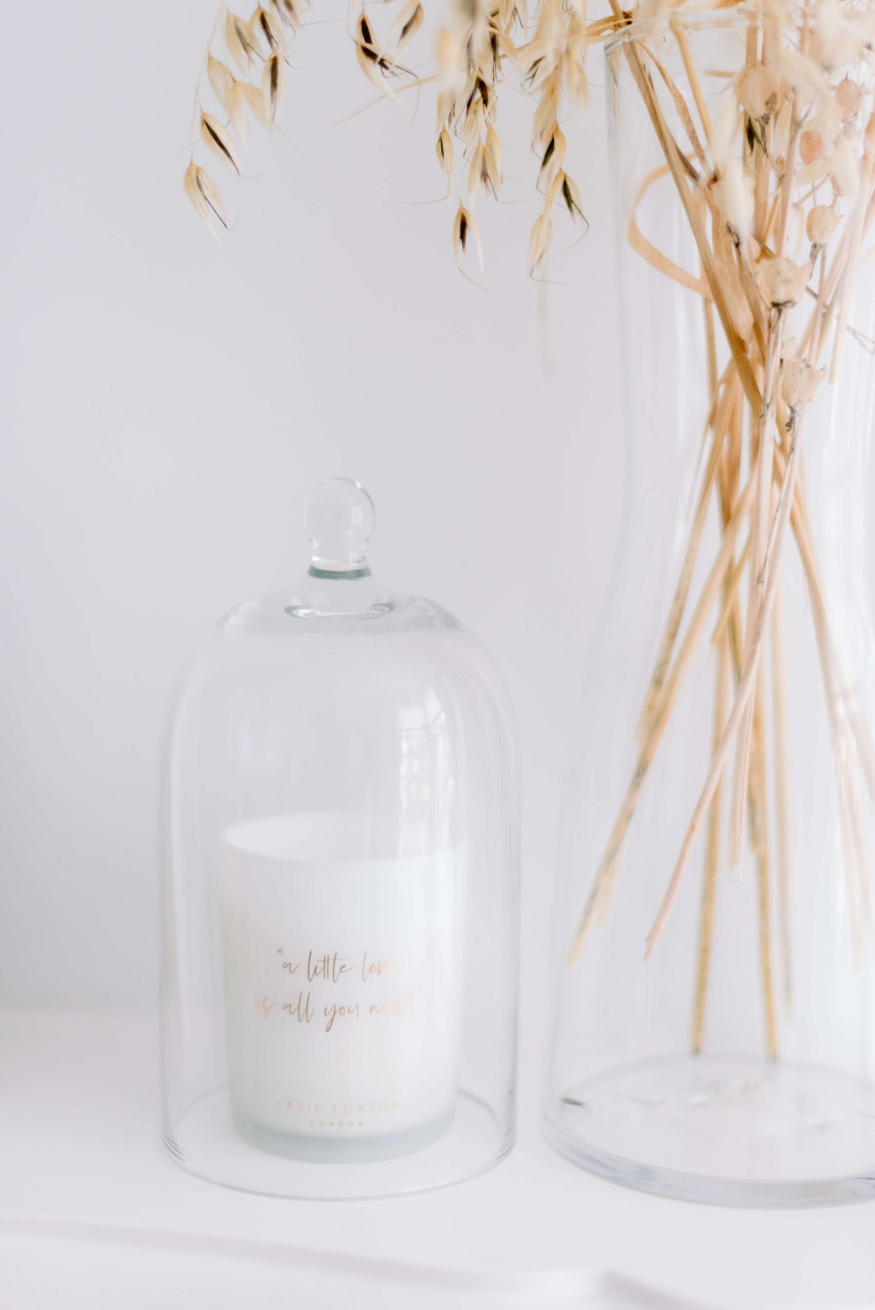 Hygge self-care theme: A little love is all you need scented candle from Katie Loxton with glass candle dome hurricane cover, dried foliage in clear vase. Photo by Cristina Ilao www.cristinailao.com