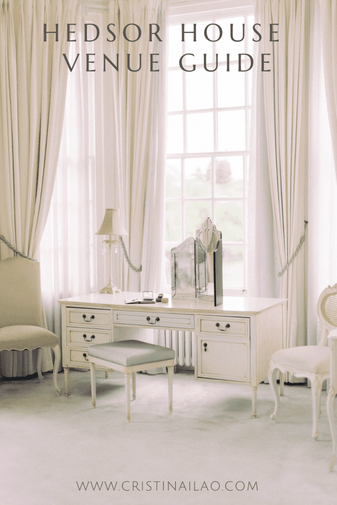 all-white room with big light-filled bay windows, heavy white drapes and white French antique furniture including a dresser, chair and three-fold mirror