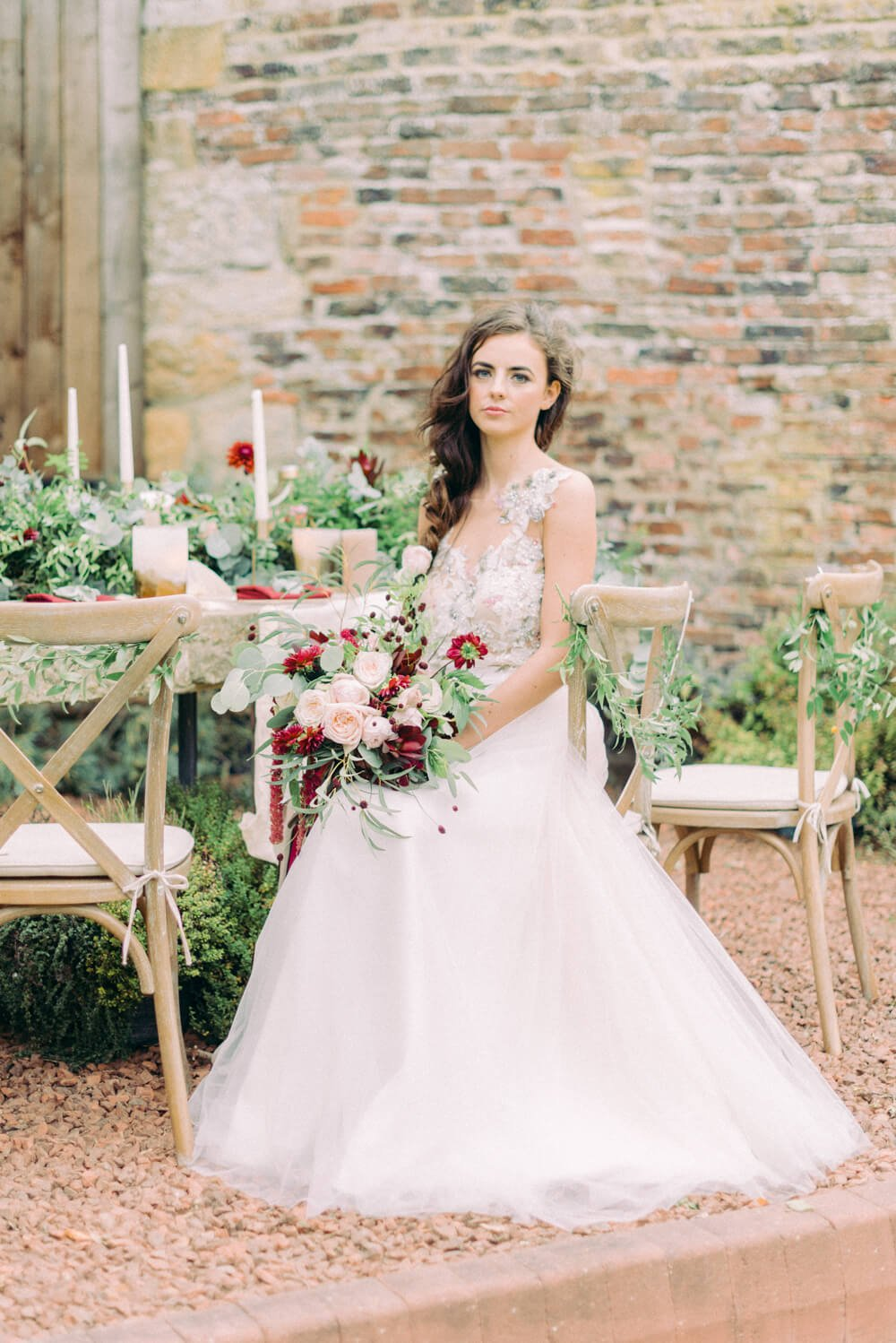 bride with wedding flowers sitting on a cross back chair