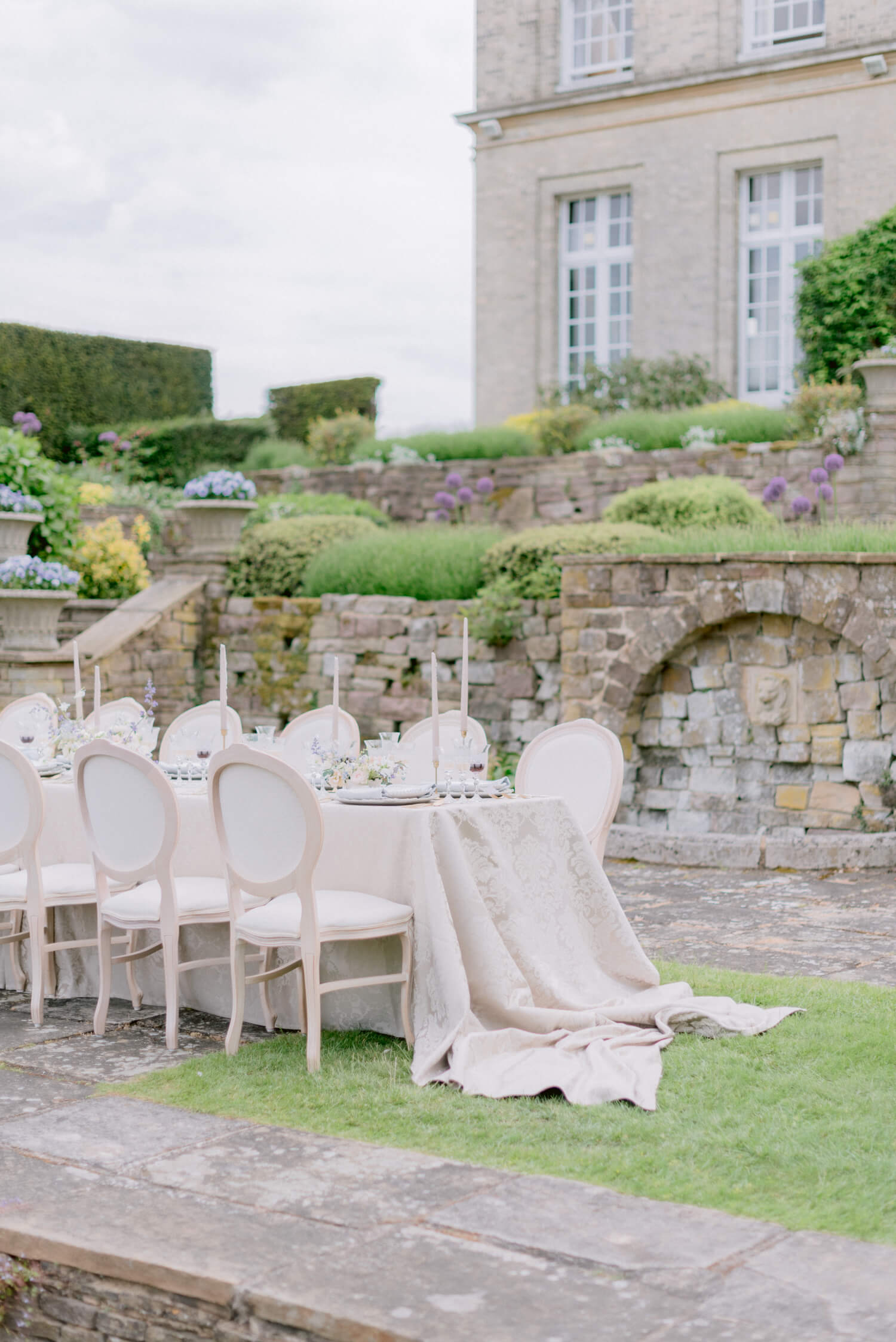 Classic English garden wedding setup. In Photo: natural wood French style antique chair with ivory cushions, crystal goblets, brass candlestick holders, tapered candles and luxury beige table cloth. Styling by Elizabeth Gopal of East Made Co. Photography by Cristina Ilao www.cristinailao.com