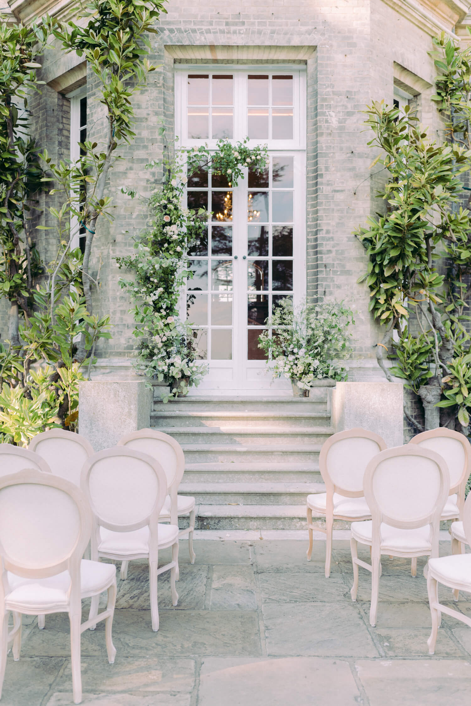 fine art garden wedding venue less than an hour from London. In photo: wedding ceremony setup outside a Georgian house with natural wood antique French style chair and ivory cushions, minimalist floral installation by UK based florist Lucy the Flower Hunter. Photography by Cristina Ilao www.cristinailao.com
