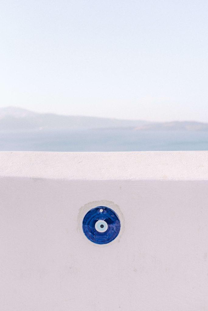 evil eye on white wall in Oia, Santorini. Photography by Cristina Ilao www.cristinailao.com