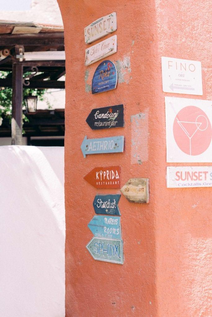 Restaurant signs in Oia Santorini Greece - Sunset, Roka, Candouni, Aethrio, Kyprida, Stardust, Marcos Rooms, Sphinx, Fino. Photography by Cristina Ilao www.cristinailao.com