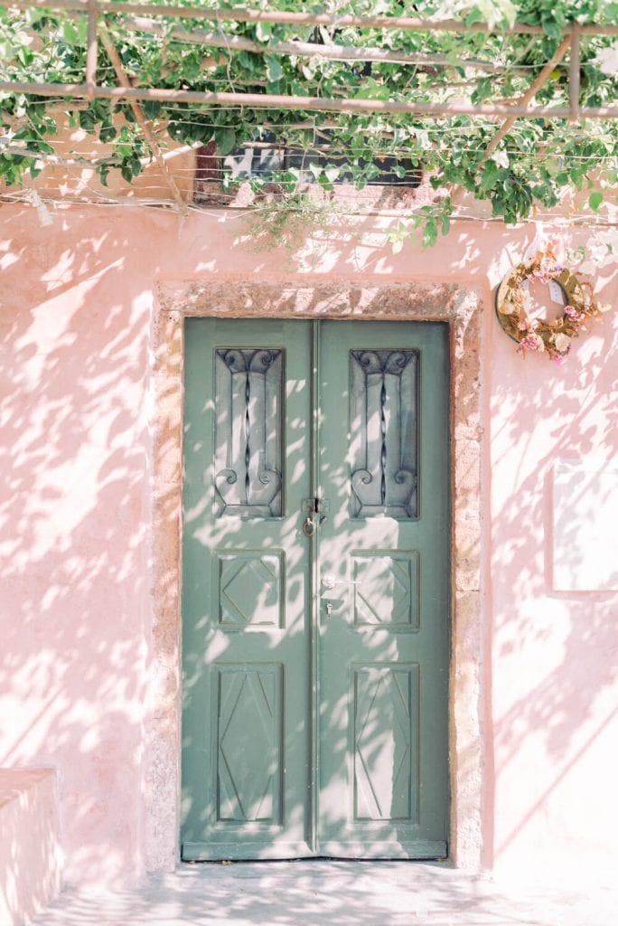 green door with blush oeach wall, Greel doors in Oia Santorini Greece with grape vines on top
