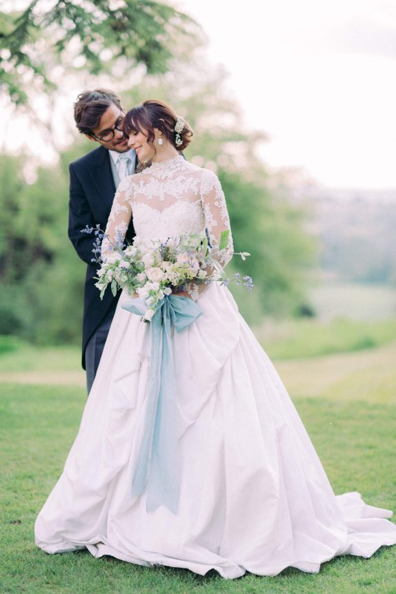 hedsor house garden wedding couple portrait: bride is wearing a custom long sleeves lace marchesa A-line wedding dress while holding spring flower bouquet in pastel colours and tied with a blue ribbon. groom is wearing an all-black long coat and trousers