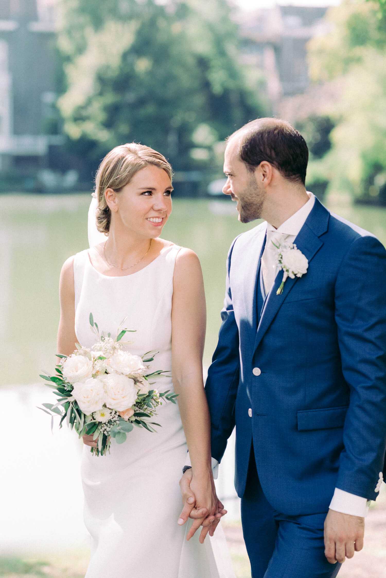 small civil destination wedding in The Hague Netherlands. Bride is wearing a simple white wedding gown with veil while holding a rose wedding bouquet while groom is wearing a royal blue suit