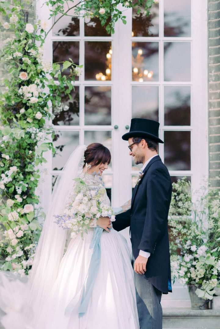 Intimate destination wedding at Hedsor House: English wedding theme in a Georgian wedding venue near London. Bride is wearing a long sleeve lace Marchesa gown and Groom is wearing a formal tuxedo long coat with top hat. Flowers by Lucy the Flower Hunter. Photo by fine art wedding photographer Cristina Ilao www.cristinailao.com