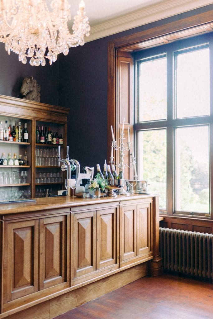 bar and cocktail area for wedding. wooden wall panels and crystal French chandelier