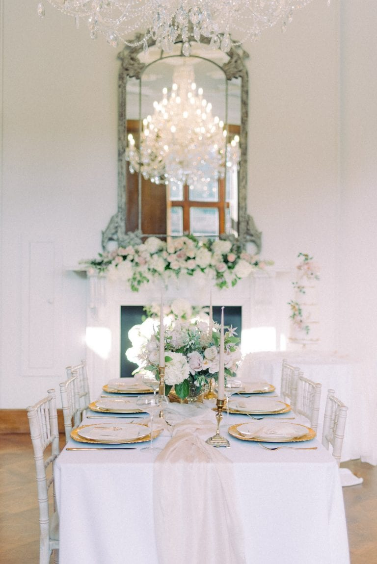 Intimate wedding setup with a pink fairytale spring theme. In photo is the grand ballroom of Thicket Priory with reception setup using antique plate chargers, heirloom candlestick holders, pink tapered candles, floral centerpiece with hydrangea blush roses and eucalyptus. white Tiffany chairs and floral backdrop on top of the marble fireplace. Crystal french antique chandelier hanging from the reception room ceiling. Photo by Cristina Ilao www.cristinailao.com