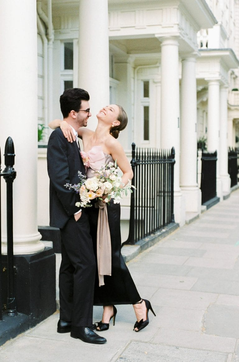 couple embracing each other and laughing outside white houses with white pillars and black fences during engagement session in Kensington London UK