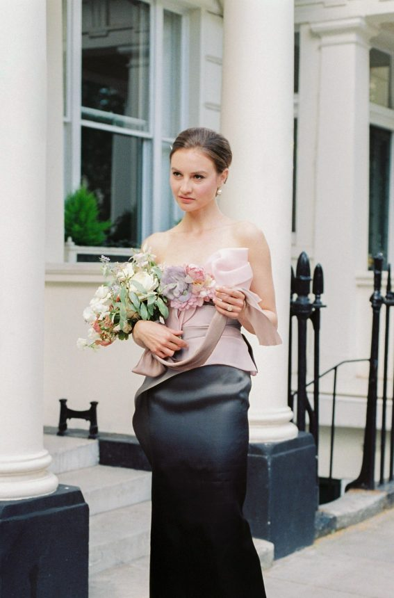 brunette female model carrying a flower bouquet with silk ribbons; On model: ombre Marchessa Notte evening gown in dusky pink, grey and black