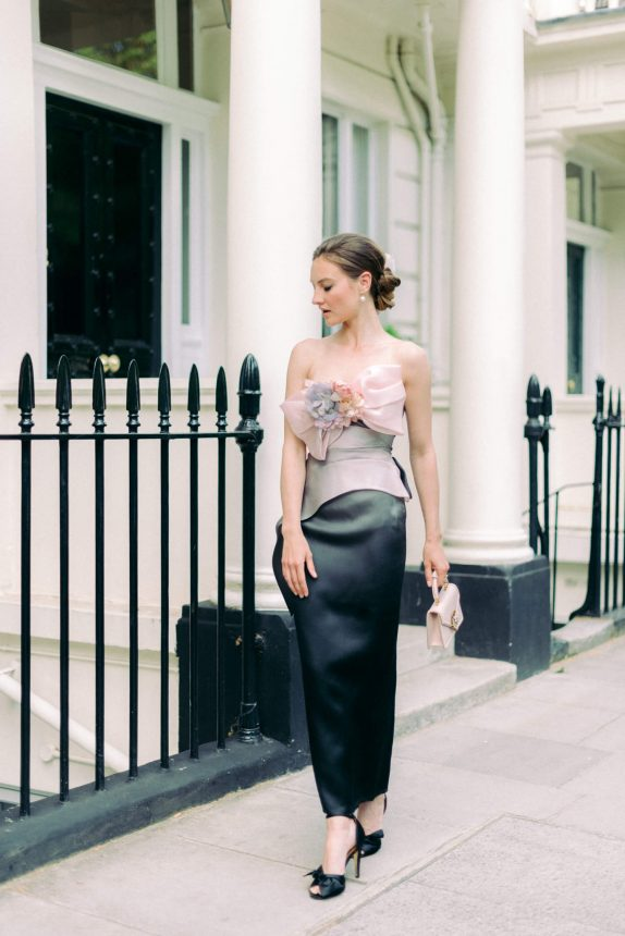 full body shot of woman walking outside the houses at London Kensington & Chelsea Borough. On woman: ombre Marchesa Notte evening dress in pink, gray and black silk with faux pink and lavander flowers