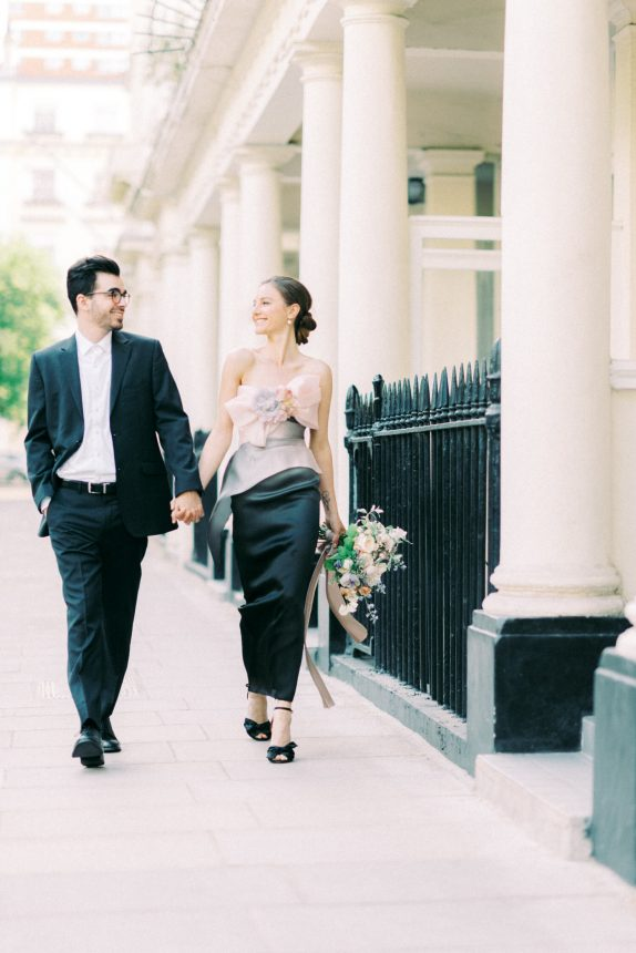 couple walking on the pavement outside white houses with pillars during engagement session in Kensington London UK