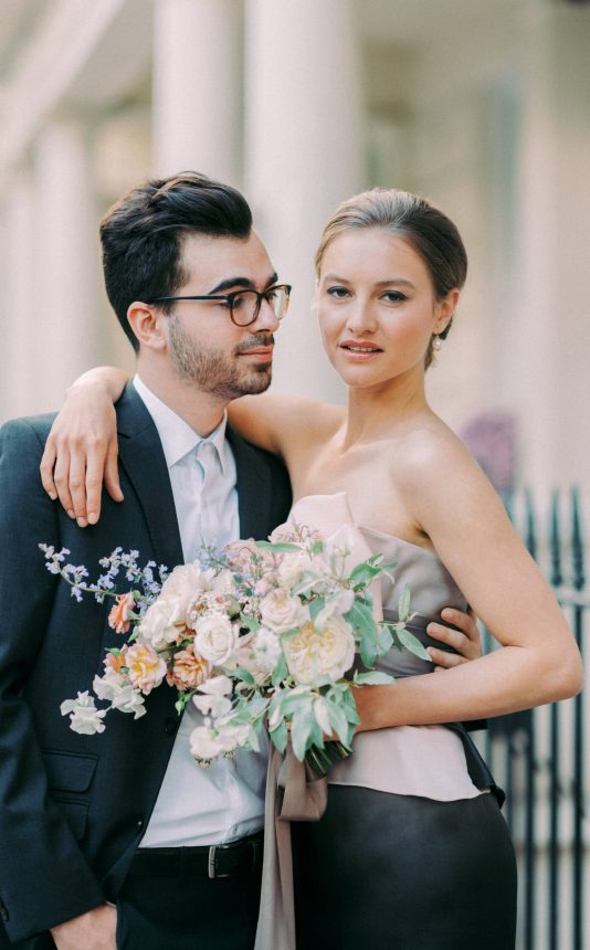 couple engagement session in Kensington London UK, man looking at woman and woman's right arm is draped around man's neck. woman is holding a bouquet of flowers with big white roses and tied with a blush pink silk ribbon