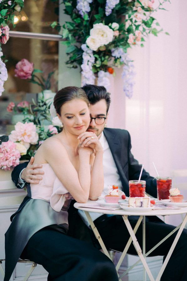 couple sitting outside Peggy Porschen Cakes in Belgravia London UK. Female brunette model wearing a Marchesa ombre evening dress in pink, grey and black. Male model wearing black suit with white shirt and black rimmed eyeglasses. On the table: sponge cupcake with cream cheese frosting, meringue and strawberry, slice of sponge cake, summer berry iced tea in plastic cups