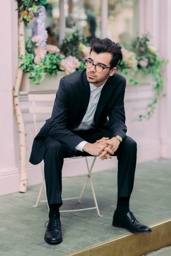 Full body portrait shot of male model sitting on a chair outside Peggy Porschen Cake Parlour in Belgravia London UK. Model has moustache and beard wearing black rimmed eyeglasses / spectacles a white shirt, brown leather watch, black formal shoes and a black suit
