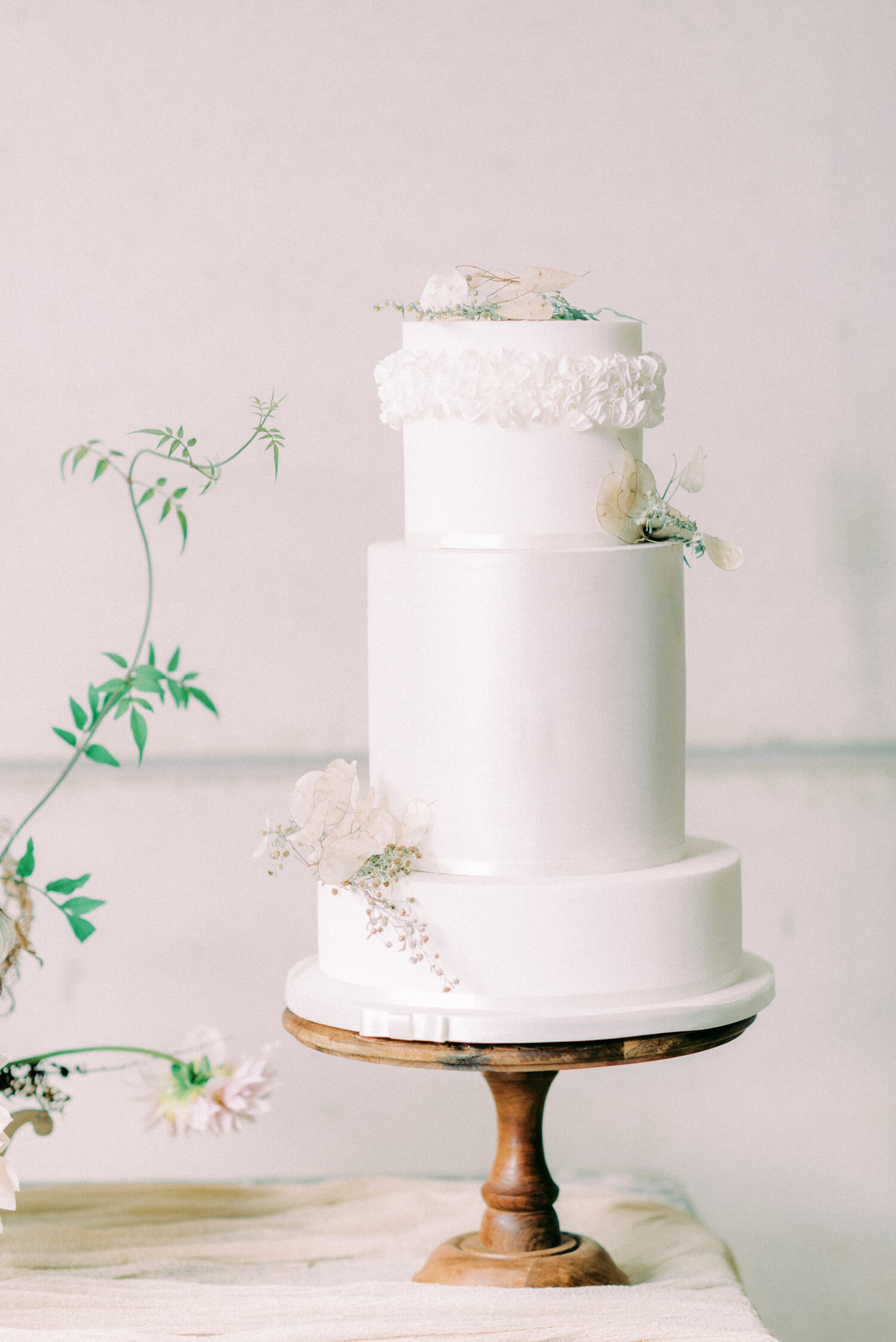 three tier simple wedding cake with ruffles and dried flowers lunaria and gypsophilia. Cake by Poppy Pickering. Photo by Cristina Ilao photography