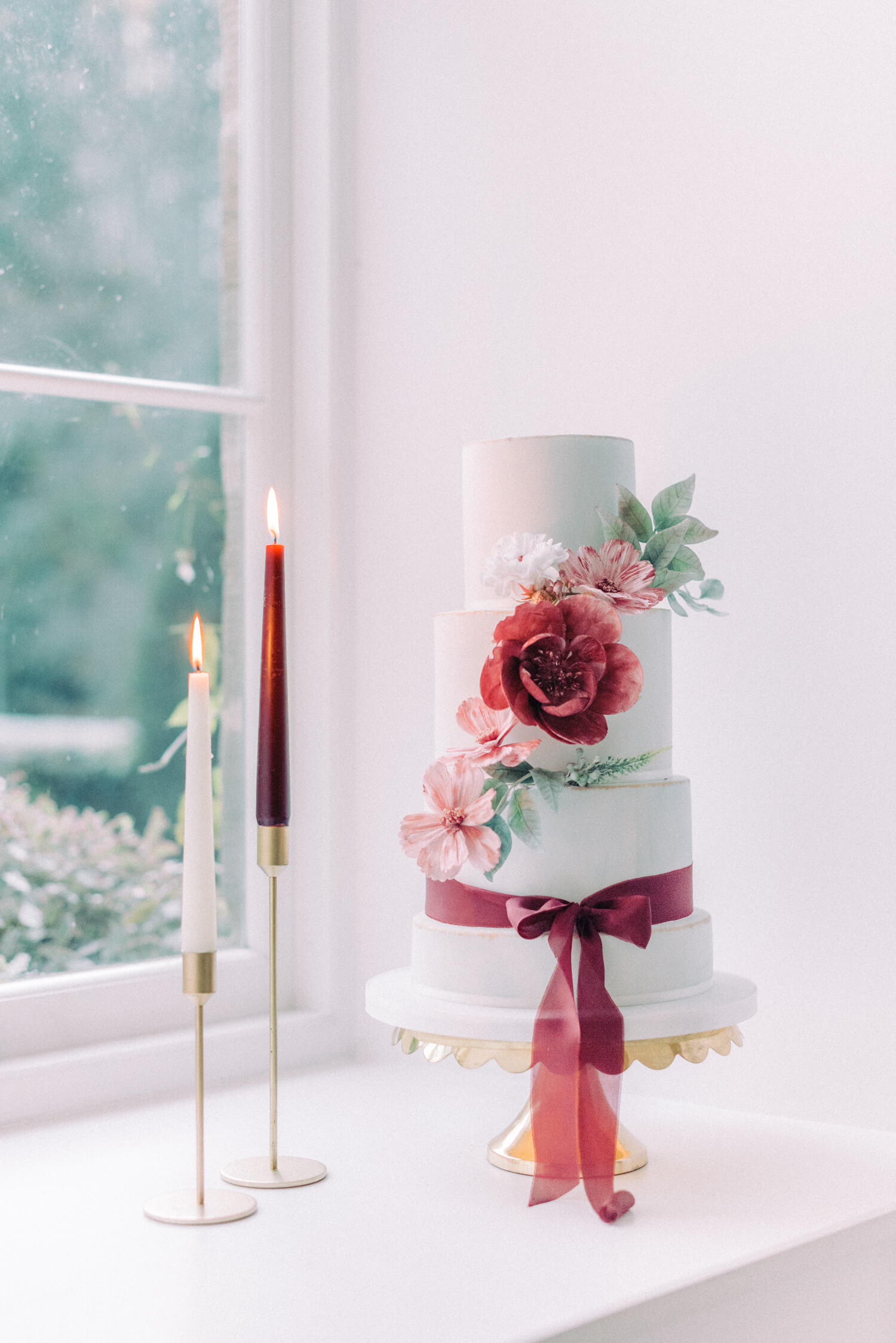 elegant christmas wedding - 3 tier fondant with burgundy and old rose flowers and hand dyed silk ribbons on a brass stand. on the left are two tapered candles on brass candlestick holders. designed  by sadie may cakes. photo by cristina ilao photography