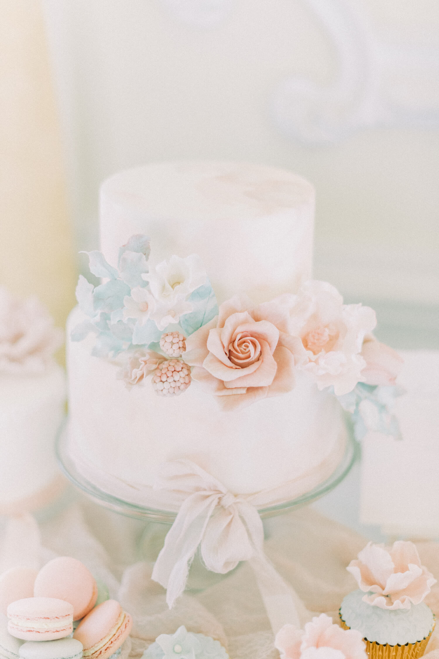 summer wedding cake ideas - peach rose with white smaller flowers, pastel berries and foliage on a two tier wedding cake tied with a hand dyed silk ribbon. Cake by Sadie May Cakes. Photo by Cristina Ilao photography