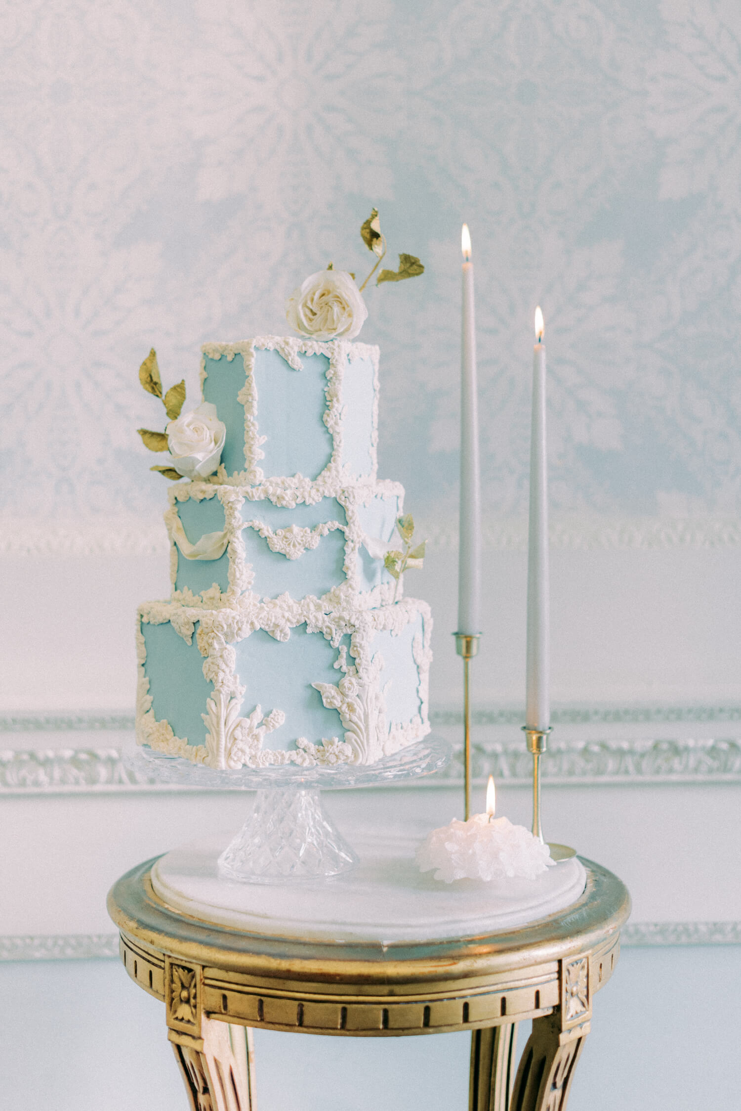 royal wedding inspired ideas - 3 tier luxury blue fondant with white molded cameo and white rose bud sugar flowers, gold leaf on a crystal cake stand, also in photo are two tulip brass candlestick holders with grey ester and erik tapered candles. Cake by Trouvaille bakery, photo by Cristina Ilao Photography, styling by East Made Event Co, Venue: Hedsor House