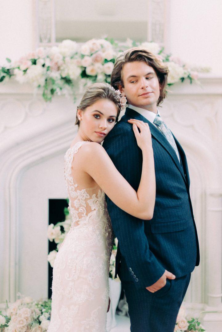 bride wearing Ellis gowns mermaid blush wedding dress and groom wearing baker's tailor navy blue pin stripe suit