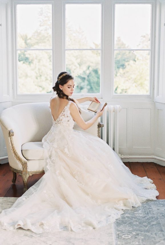 Victorian inspired editorial: bride sitting on a french antique chair and wearing an a line wedding dress with sequins and 3d flowers while reading antique literature books