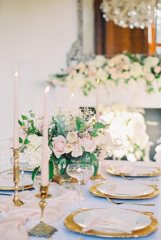 table setting with roses and hydrangea; gold charger plates and plain white plates with gold utensils, blush silk table runner- Photo by fine art wedding photographer Cristina Ilao www.cristinailao.com