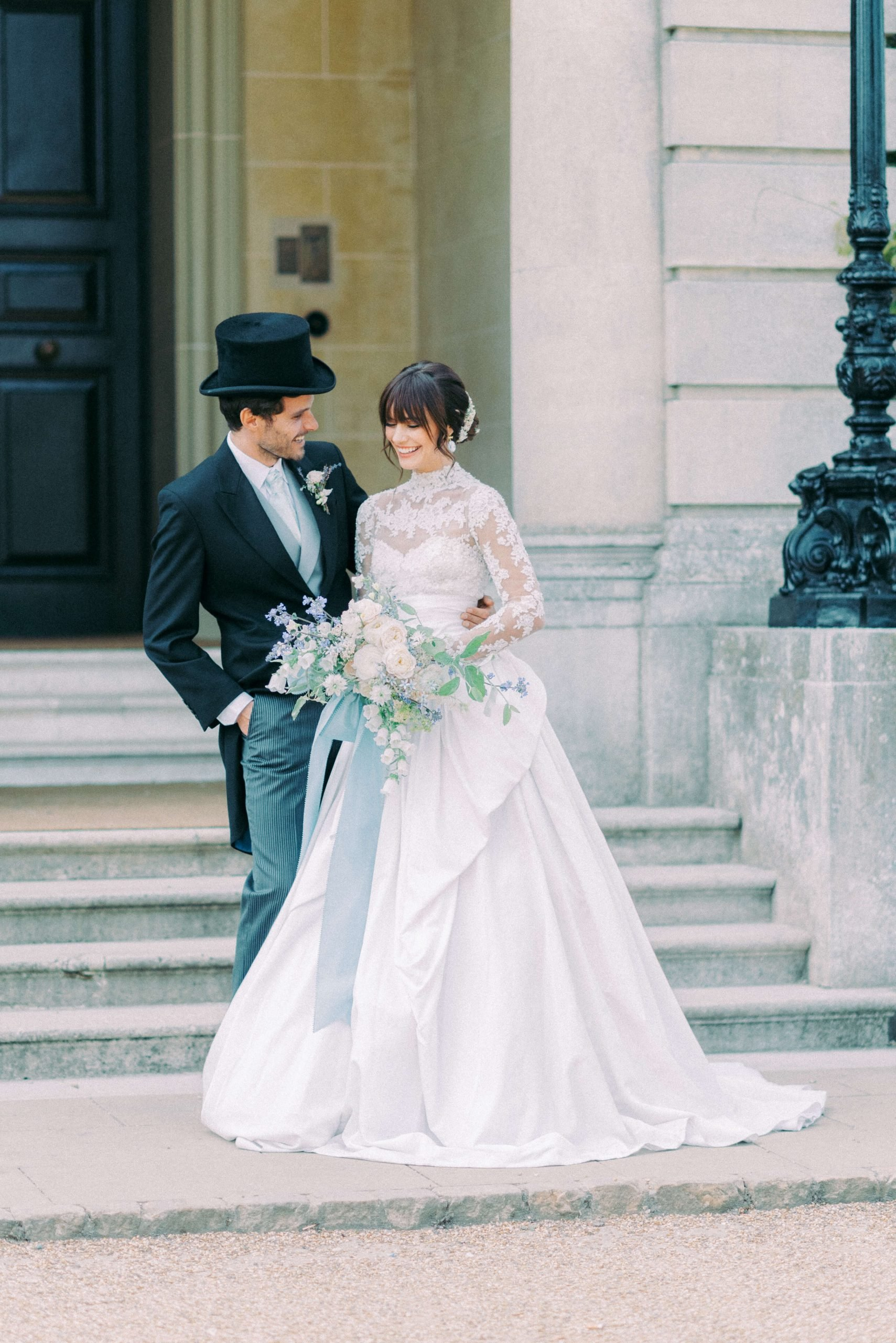 intimate wedding in the UK - bride wearing Marchesa high neck long sleeves a line lace wedding gown and groom wearing long black coat, top hat and pinstripe trousers at the front steps of Hedsor House wedding venue near London. Photo by Cristina Ilao www.cristinailao.com